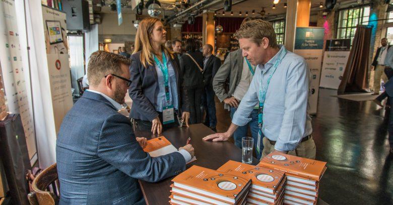 """Signature du livre """"Inform, transforme, & Outperform"""" écrit par John Horodyski au Dam Summit, Day1, Berlin, Allemagne"""